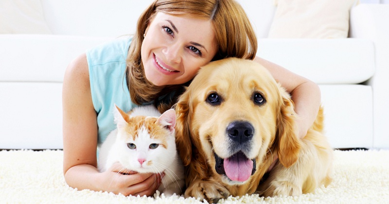 A happy pet owner with cat and dog